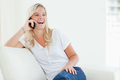 A laughing woman on her phone as she sits on the couch Stock Image