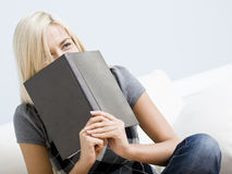 Laughing Woman Holding a Book Stock Photos