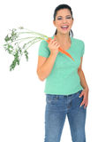 Laughing Woman Holding Carrot. Diet concept. a woman holding fresh carrot on her right hand. isolated on white royalty free stock image