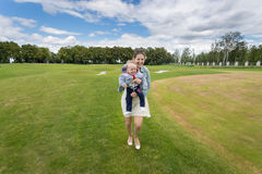 Laughing woman holding cheerful baby boy and having fun on grass royalty free stock images