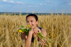 Laughing woman holding flowers in a wheat field Stock Image