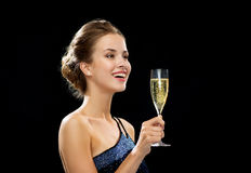 Laughing woman holding glass of sparkling wine. Party, drinks, holidays, luxury and celebration concept - laughing woman in evening dress with glass of sparkling Stock Image