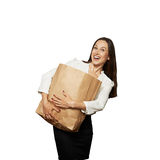 Laughing woman holding heavy paper bag Royalty Free Stock Images