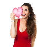 Laughing woman holding a love heart over her eye. Royalty Free Stock Photos
