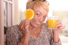 Laughing woman holding an orange to her eye Royalty Free Stock Photos