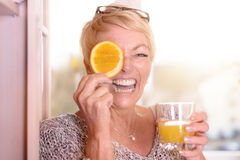 Laughing woman holding an orange to her eye. Laughing vivacious middle-aged blond woman holding an orange slice to her eye while holding a glass of freshly Royalty Free Stock Photo