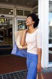 Laughing woman holding shopping bags outside mall. Portrait of laughing woman holding shopping bags outside mall Royalty Free Stock Image