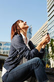 Laughing woman holding smart phone with earphones Stock Photos