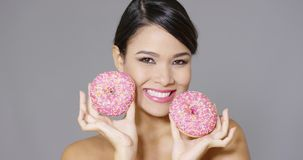 Laughing woman holding two pink donuts to her eyes stock video