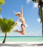 Laughing woman jumping on the beach Royalty Free Stock Image