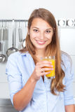 Laughing woman in the kitchen drinking orange juic Royalty Free Stock Images