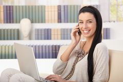 Laughing woman with laptop on call Stock Photos