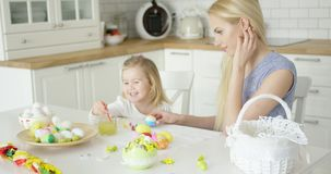 Laughing woman and little girl coloring eggs stock video footage