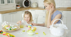 Laughing woman and little girl coloring eggs Royalty Free Stock Images