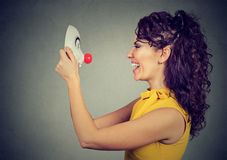 Laughing woman looking at clown mask. Isolated on gray wall background Stock Photos