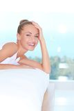 Laughing woman looking over back of sofa Royalty Free Stock Photo