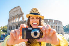Laughing woman looks up from taking photo with Colosseum behind Stock Images