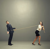 Laughing woman lugging man in perplexity Stock Photo