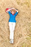 Laughing woman lying down on grass in meadow. Young girl lying on grass in field. Beautiful woman in sport clothes resting with backpack under head. Happy Stock Images