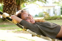 Laughing woman lying in hammock in front of palm tree. Portrait of laughing woman lying in hammock in front of palm tree Stock Images