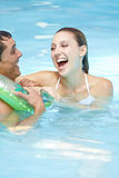 Laughing woman with man in floating ring Royalty Free Stock Photo