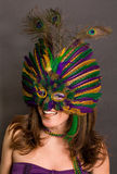 Laughing Woman in Mask and Makeup. A portrait of a beautiful young woman wearing a Mardi Gras mask and matching makeup Royalty Free Stock Photos
