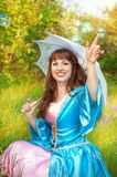 Laughing woman in medieval dress and bubble blowers Royalty Free Stock Image