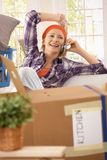 Laughing woman with mobilephone at moving. Laughing woman taking break at moving house, talking on mobilephone Stock Photos