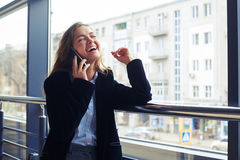 Laughing woman next to the window talking on phone Royalty Free Stock Photo