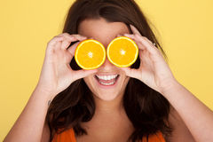 Laughing Woman With Orange Slices Over Eyes Stock Photography