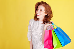 Laughing Woman Out Shopping. Laughing redhead woman standing with three colourful shopping bags over her shoulder Stock Images