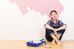 Laughing woman painting her wall in pink Royalty Free Stock Photos