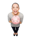 Laughing woman with piggy bank Royalty Free Stock Photography