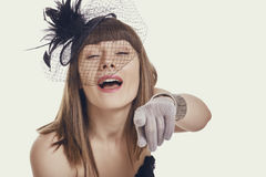 Laughing Woman Pointing Finger. Portrait of an amused beautiful young woman wearing a black vintage style light feather hat, net veil and gloves while pointing stock image