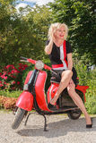 Laughing woman posing in fashionable summer dress on a scooter Stock Image