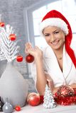 Laughing woman preparing for Christmas. Portrait of attractive laughing woman in Santa hat preparing decoration for Christmas Royalty Free Stock Photo