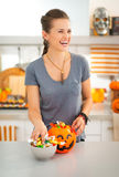 Laughing woman preparing halloween trick or treat candy for kids Stock Images