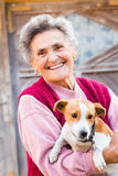 Laughing Woman with Puppy. Laughing elderly woman with her kind little puppy outdoors stock photography