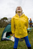 Laughing woman in raincoat camping in field Stock Photo