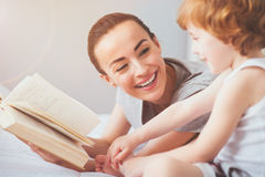 Laughing woman reading a book to her son Stock Image