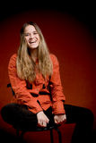 Laughing woman on red. Portret of young female student on red background in studio royalty free stock photography