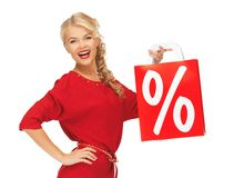 Laughing woman in red dress with shopping bag Stock Image