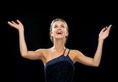 Laughing woman rising hands and looking up. People, happiness, holidays and glamour concept - laughing woman rising hands and looking up over black background Royalty Free Stock Photo