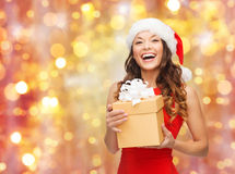 Laughing woman in santa hat with christmas gift. Christmas, x-mas, winter, people and celebration concept - laughing woman in santa hat and red dress with gift Royalty Free Stock Photos