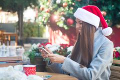 Laughing woman in Santa hat texting near Cristmas tree in cafe outside Stock Photos