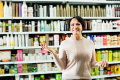 Laughing woman selecting hair care products. In shop and smiling royalty free stock photo