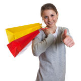 Laughing woman with shopping bags showing thumb up Stock Images