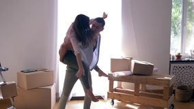Laughing woman sitting on back of boyfriend and spinning among boxes during relocation to housing. Laughing woman sitting on back of boyfriend and spinning among stock footage