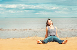 Laughing woman sitting on the beach Stock Photo