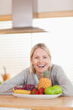 Laughing woman sitting behind plate of fruits Stock Photo